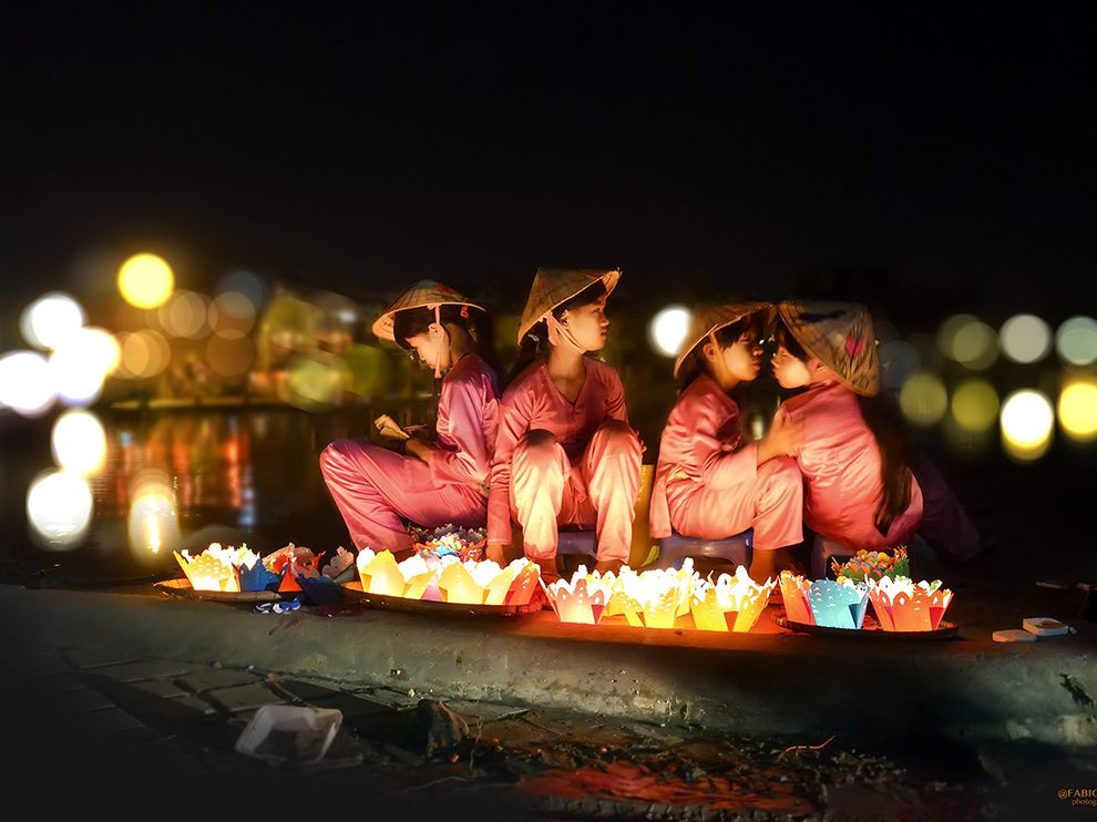 Picture of young girls selling floating candles in Hoi An, Vietnam
