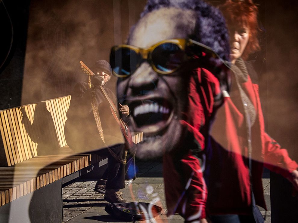 Picture of a street performer reflected in a window with an image of Ray Charles, Nova Gorica, Slovenia