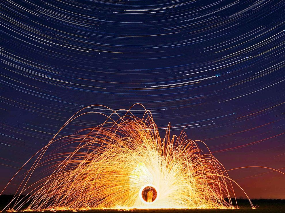 Picture of a man creating fire trails using burning wool on a starry night, Salcombe, England