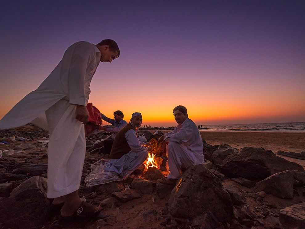 Picture of men sitting by a fire on the beach, United Arab Emirates