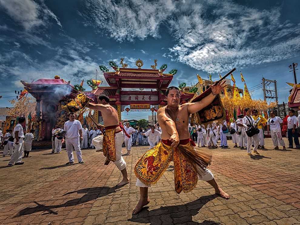 Picture of men performing a ceremony at the Vegetarian Festival in Phuket, Thailand