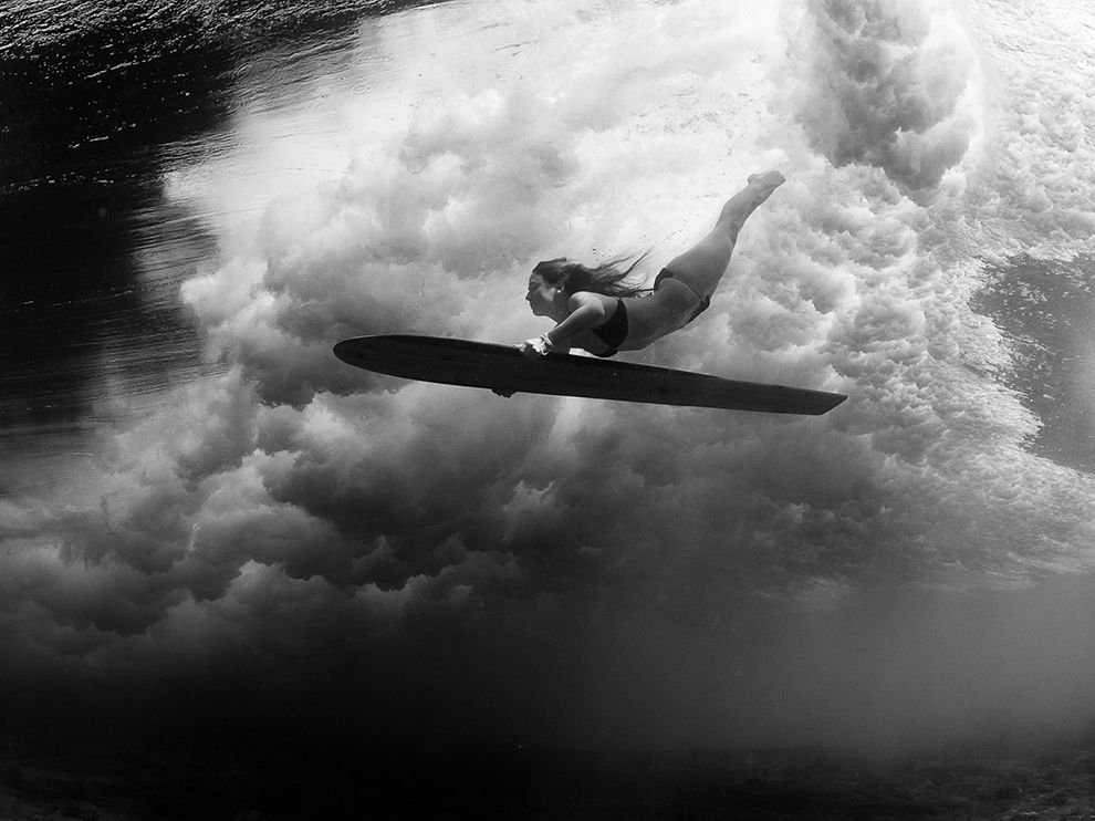 Picture of a surfer duck diving under a wave with a wooden alaia, Kona, Hawaii