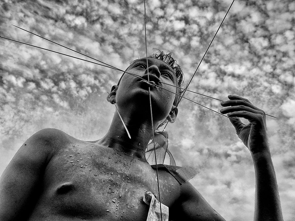 Picture of a religious man with pins piercing his face in Bengal, India