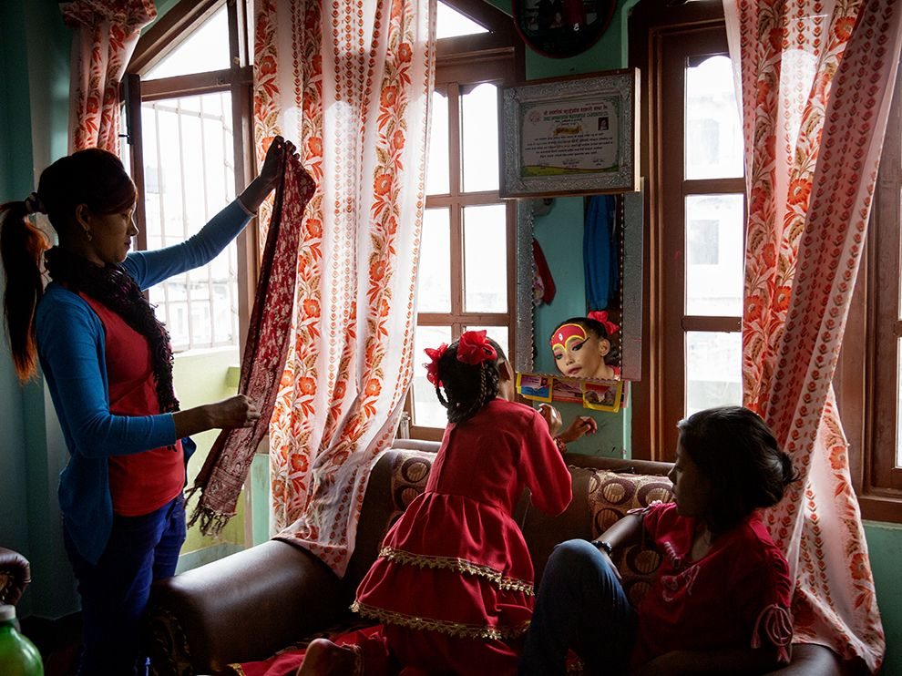 Picture of a Newari living goddess putting on makeup, Nepal