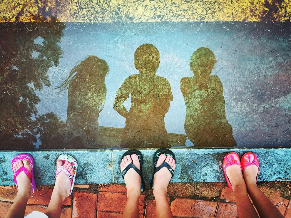 Picture of children looking at their reflection in a puddle