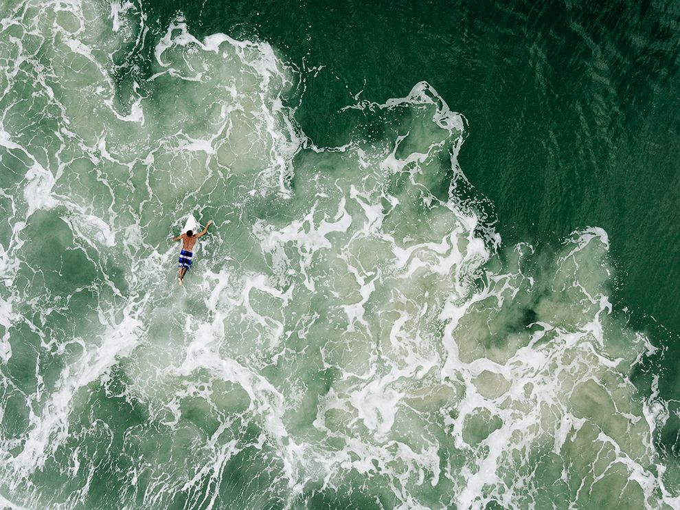 Picture of a surfer paddling out from Praia Mole beach in Brazil