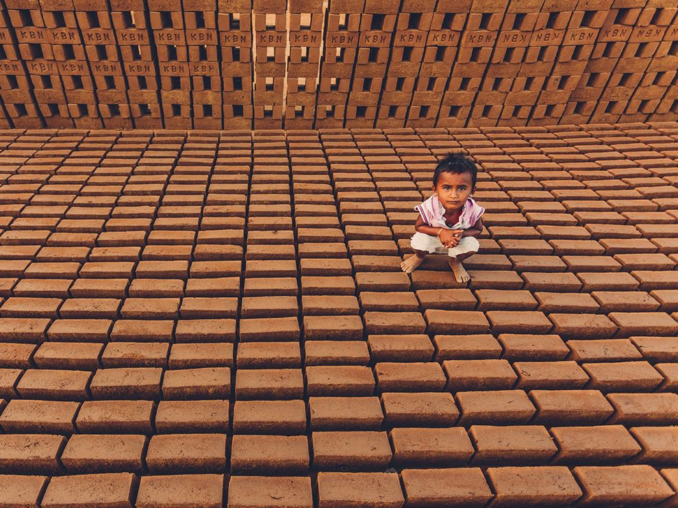 Picture of a young girl squatting on a brick palette, India
