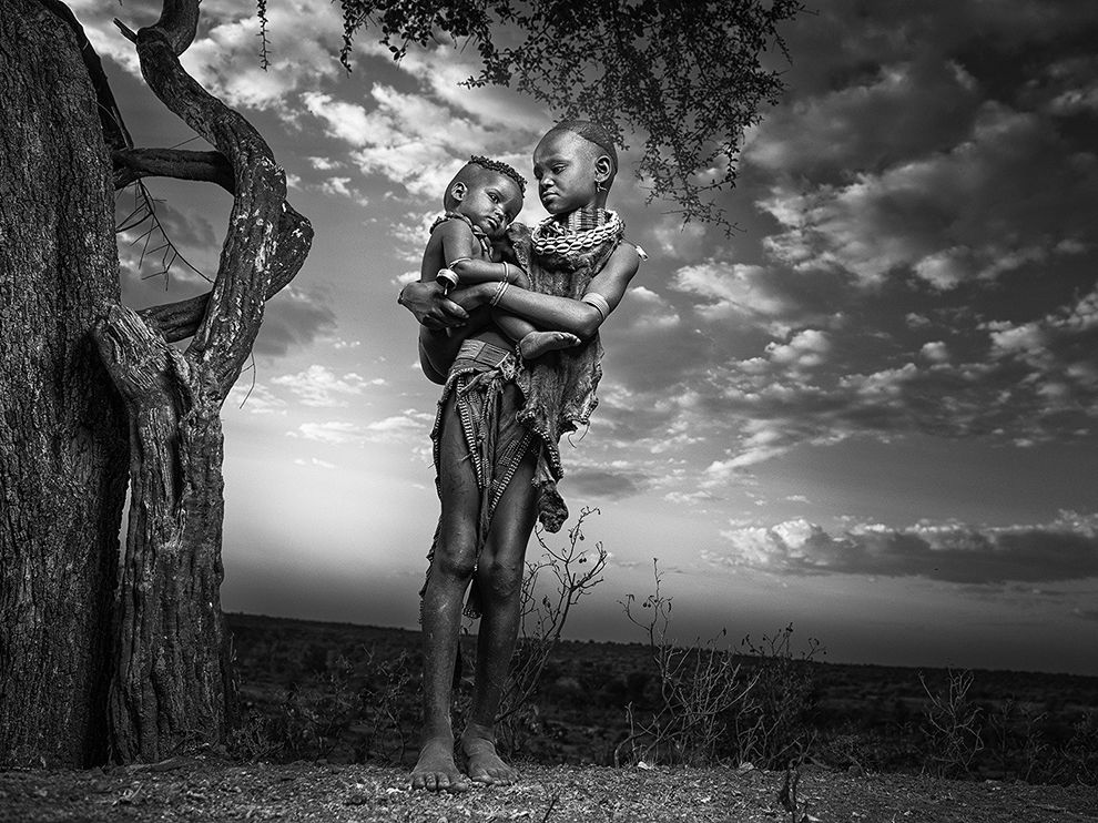 Picture of young woman carrying her infant sibling, Ethiopia