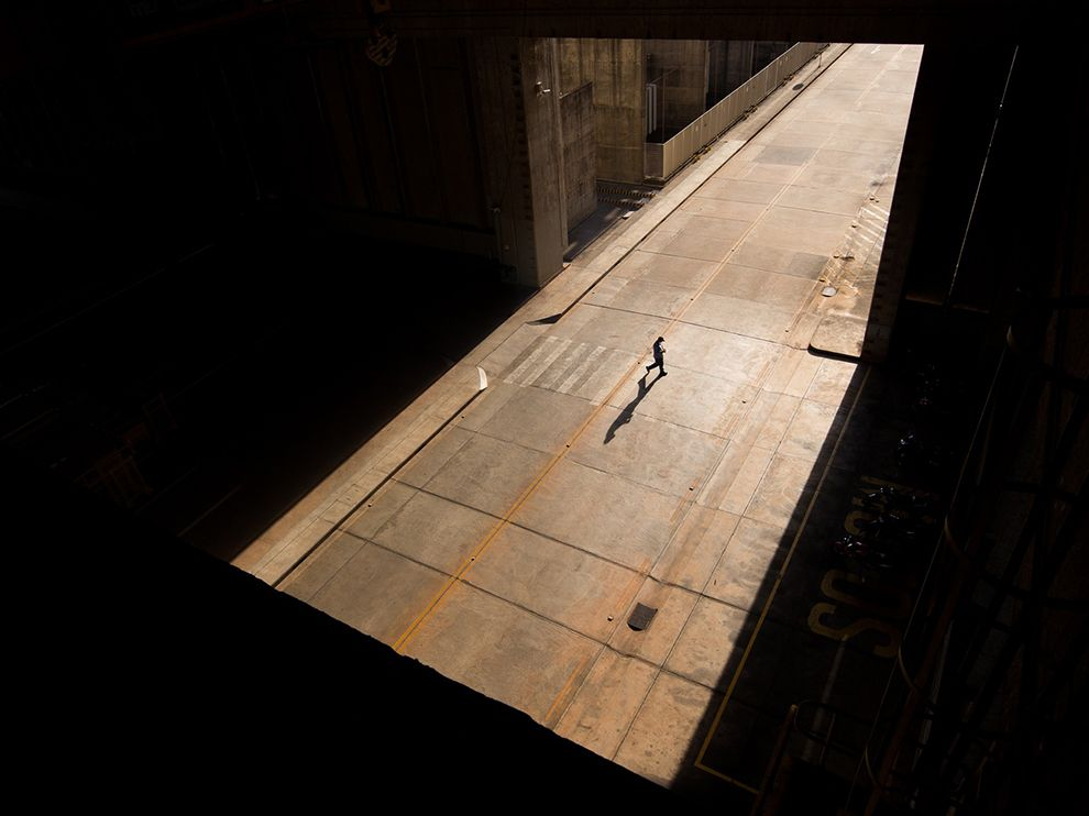 Picture of a man crossing the road from shadow to light