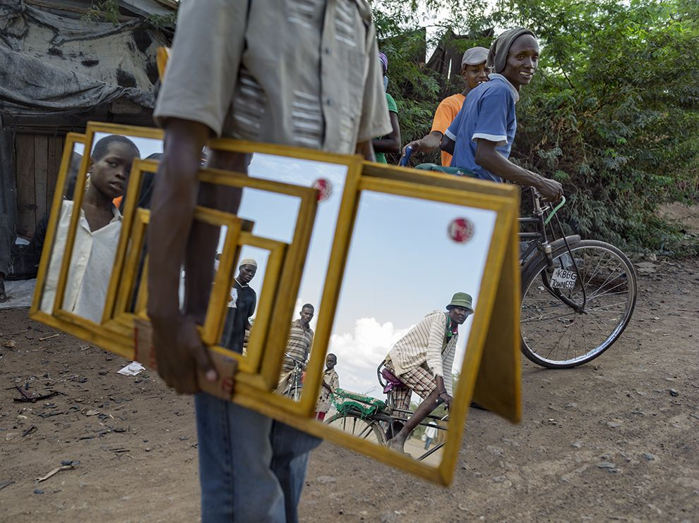 Picture of a man carrying mirrors with people reflected in them, Kenya