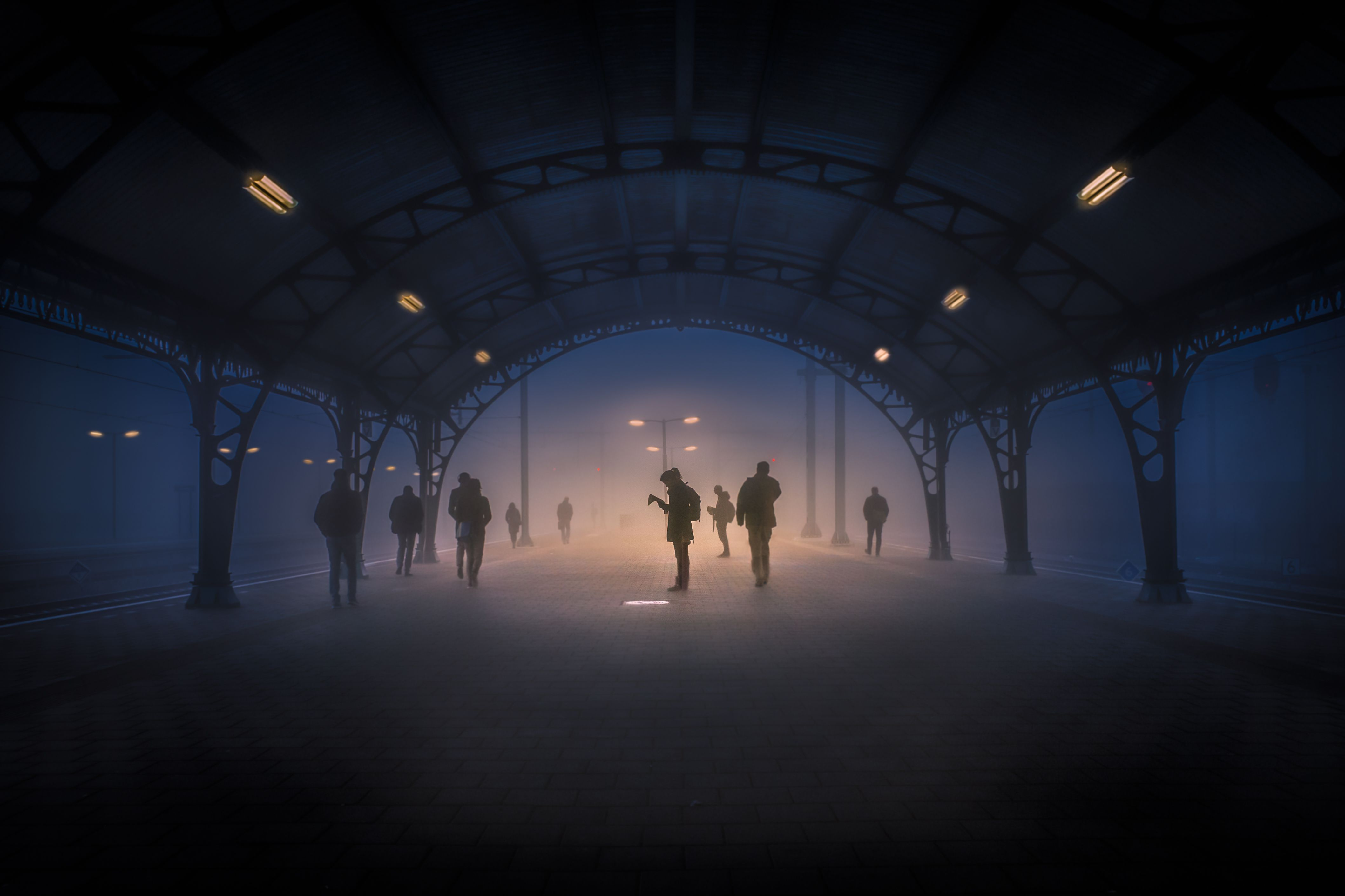 "Morning commuters wait for their train at a stop in North Brabant, Netherlands. ""It was like a silent movie,"" says Your Shot photographer Takeshi Ishizaki. ""People were appearing from the mist very quietly and disappearing into it again."""