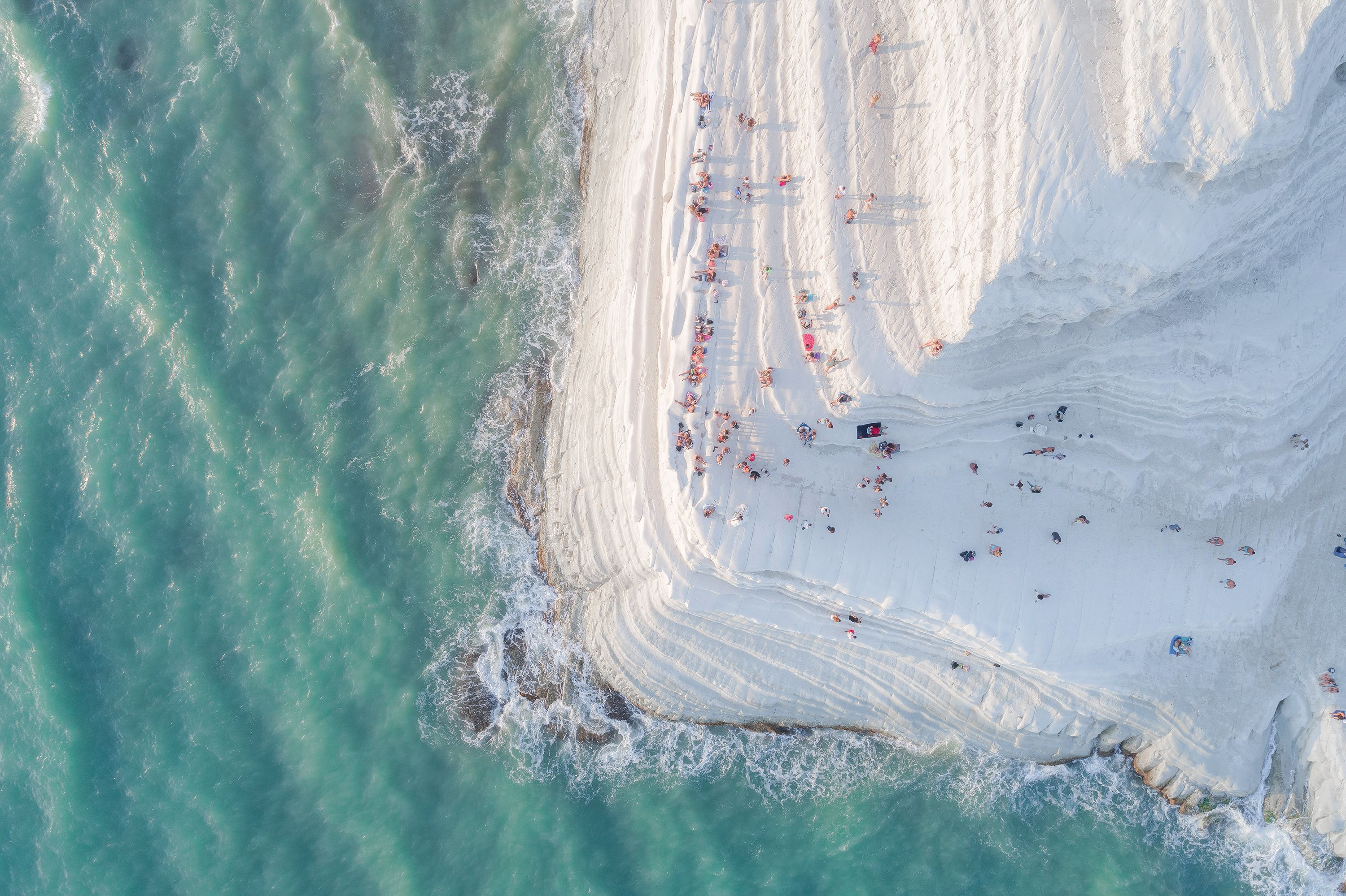"This white cliff in Sicily is called ""Scala dei Turchi,"" or the Turkish Steps. Natural erosion has softened the limestone and marl cliff, and the aerial view of visitors reminds Your Shot photographer Placido Faranda of ""a big meringue covered with sprinkles."""