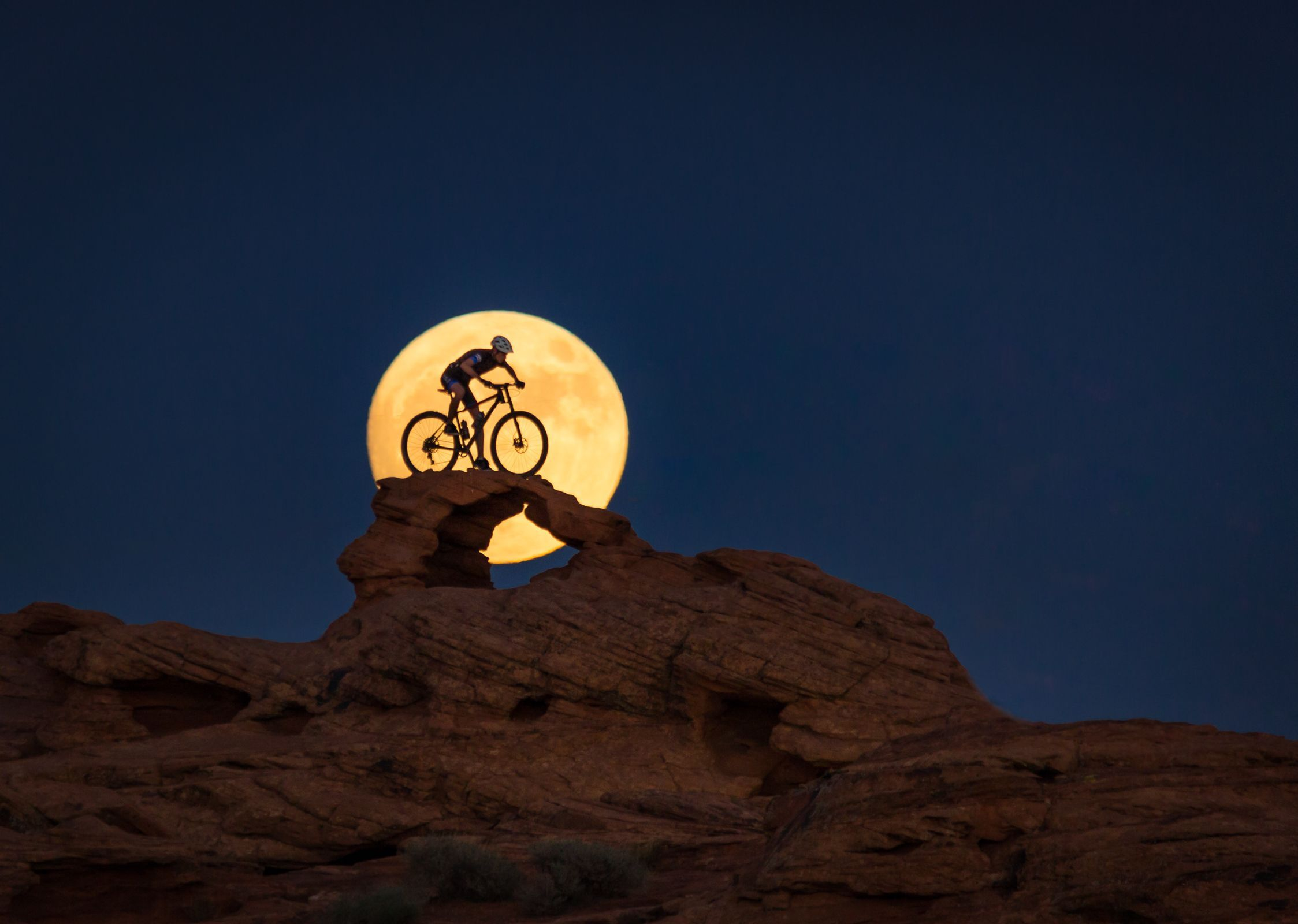 "Your Shot photographer Amy Osness learned the value of persistance while photographing her son on his mountain bike in Saint George, Utah. ""This is our second attempt at capturing this image,"" she says. ""I learned a lot the first time around and was able to create the image I had envisioned. My son balanced himself a top the narrow arch long enough for me to take a few shots just as the moon was rising behind him."""