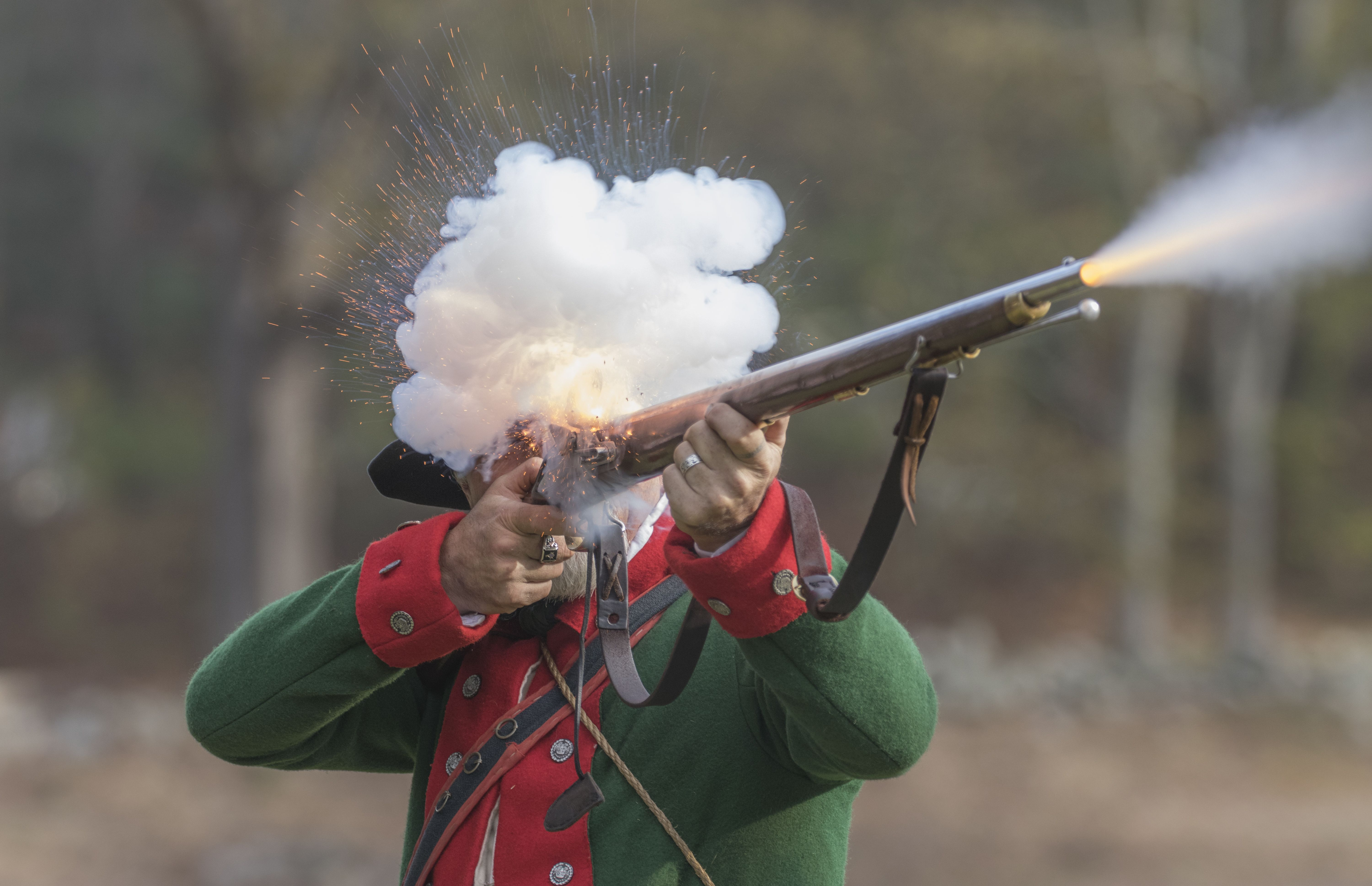 A Revolutionary War reenactor, representing a British soldier, fires his musket at a reenactment of the Battle of the Red Horse Tavern in Sudbury, Massachusetts. The annual reenactments involve several hundred people posing as soldiers on both sides of the battle.