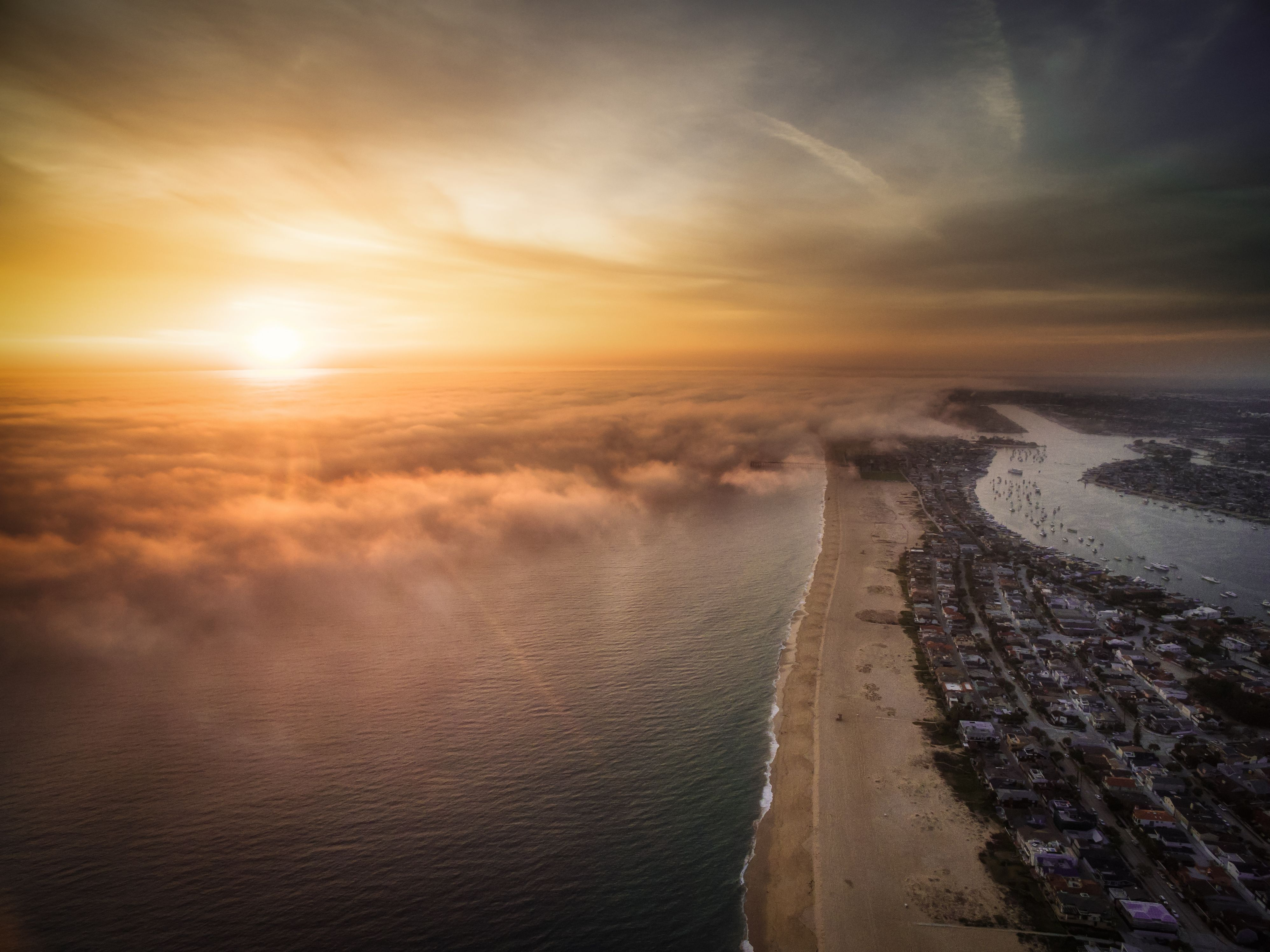 Flying above low clouds, a drone captures a beautiful sunset over Newport Beach, California. The Pacific Ocean controls Newport Beach's mild climate, with cooler summers and warmer winters.