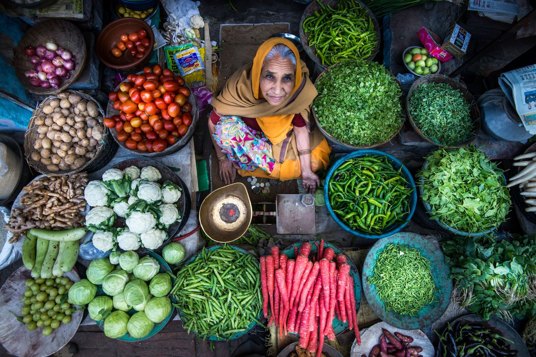 A vegetable vendor poses with her produce in Jodhpur, Rajasthan, India. She has set up shop in the same spot every day for more than thirty years, her grandson told Your Shot photographer Steve Demeranville.