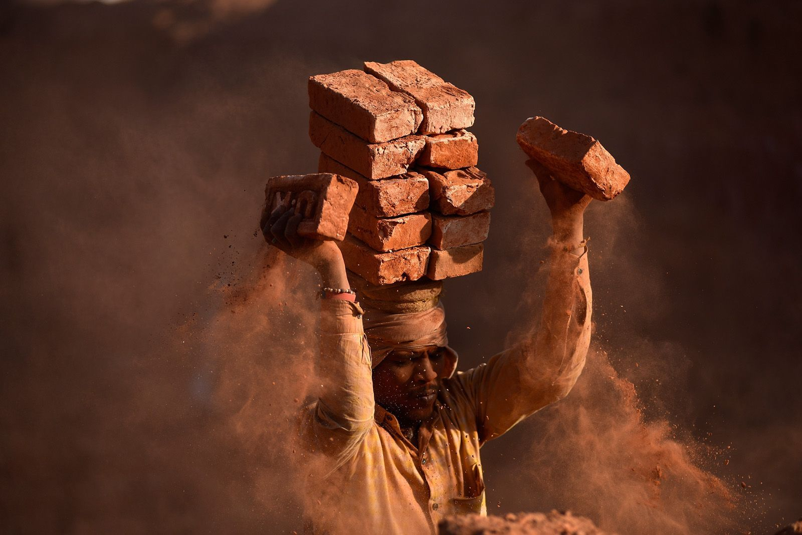 A migrant laborer from India balances bricks on his head at a brick factory in Lalitpur, Nepal. The factory workers can carry up to 16 bricks on their heads at a time.