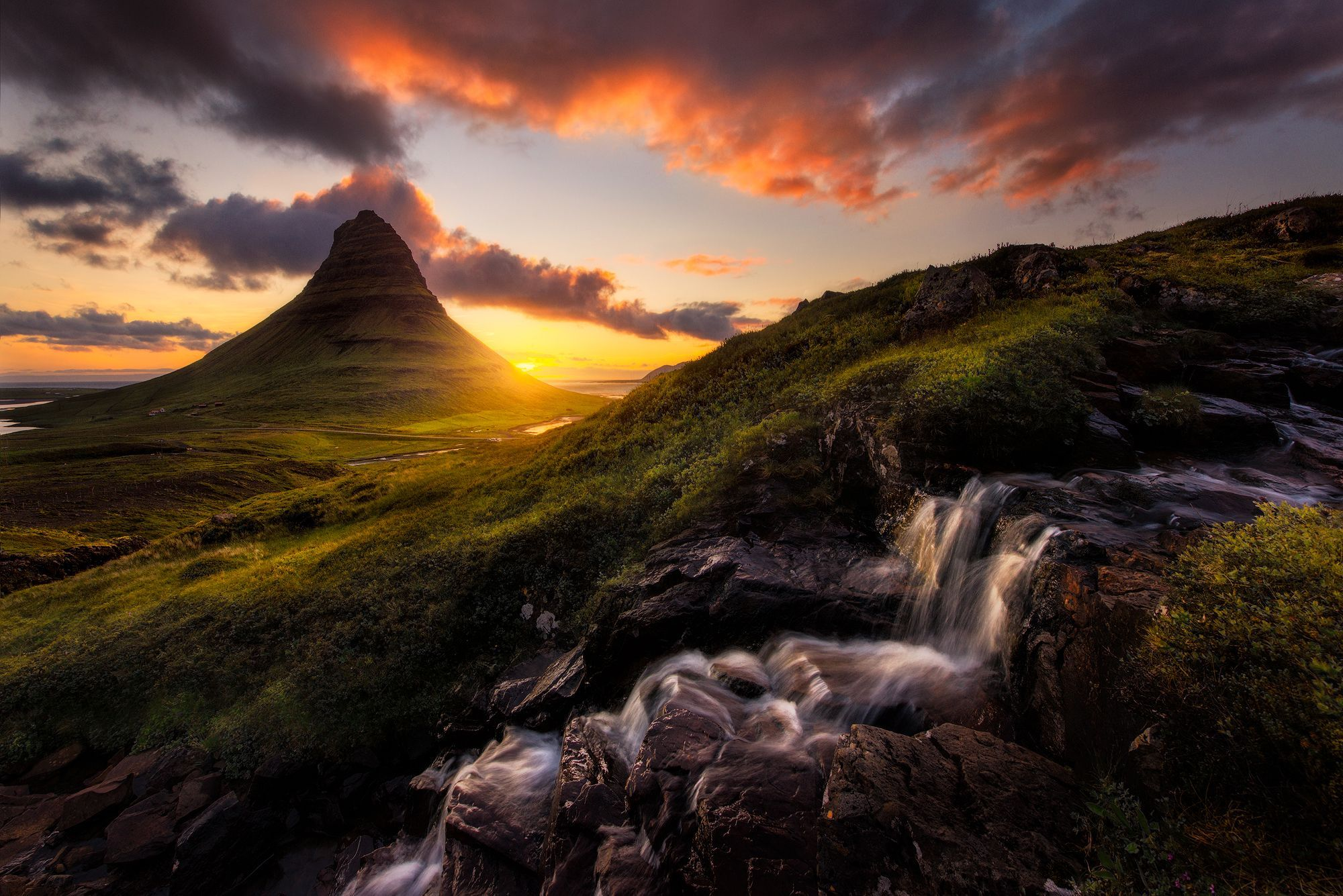 The sun rises behind Kirkjufell, arguably Iceland's most famous mountain. The mountain stands 1,500 feet high on its own small peninsula.
