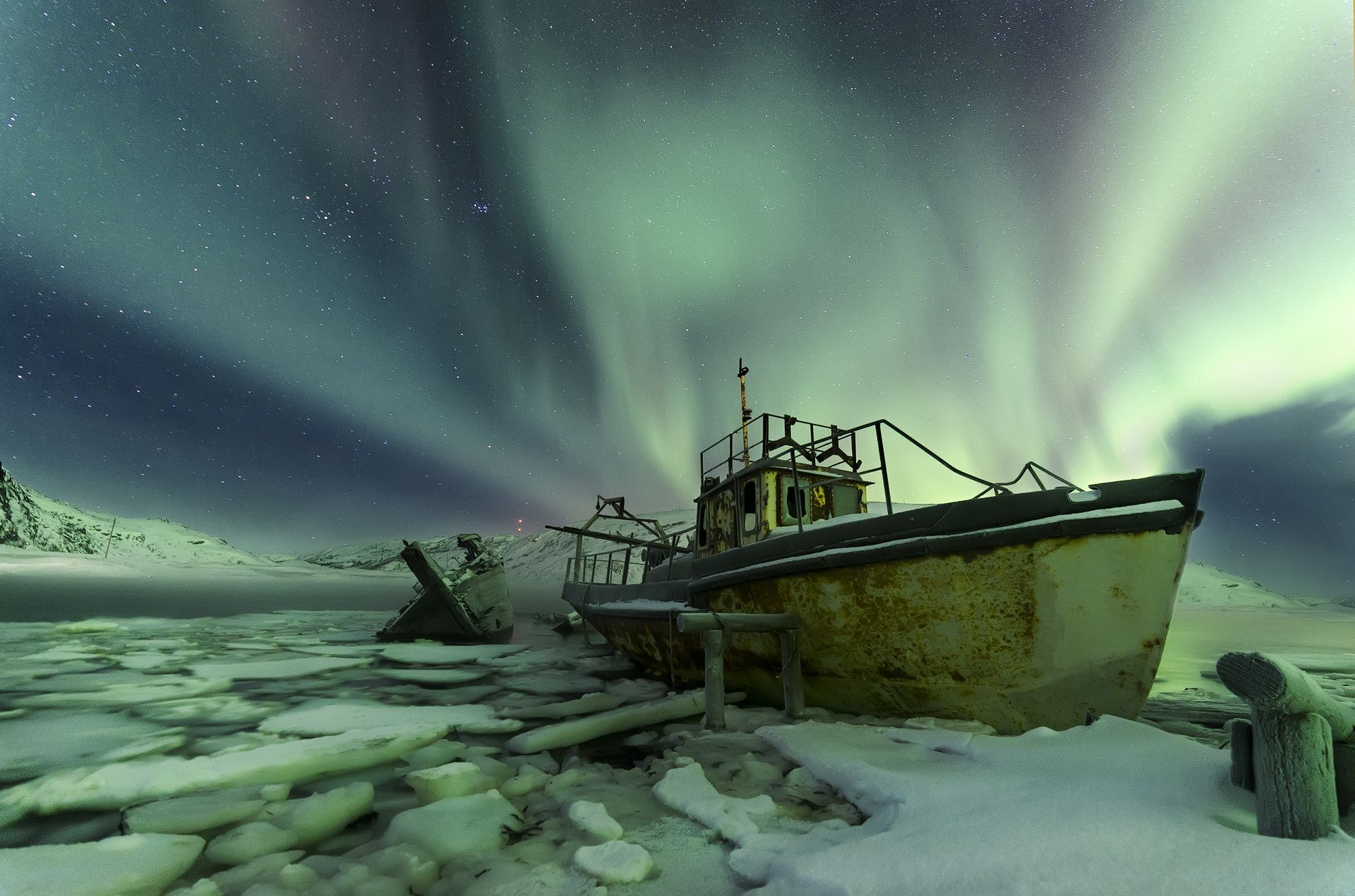 The northern lights glow behind old, abandoned ships in the village of Teriberka, Russia. Once a hub for shipping and fishing, Teriberka experienced an economic downfall that started when the town's administration was taken over by nearby Severomorsk, the home of the Russian Northern Fleet.