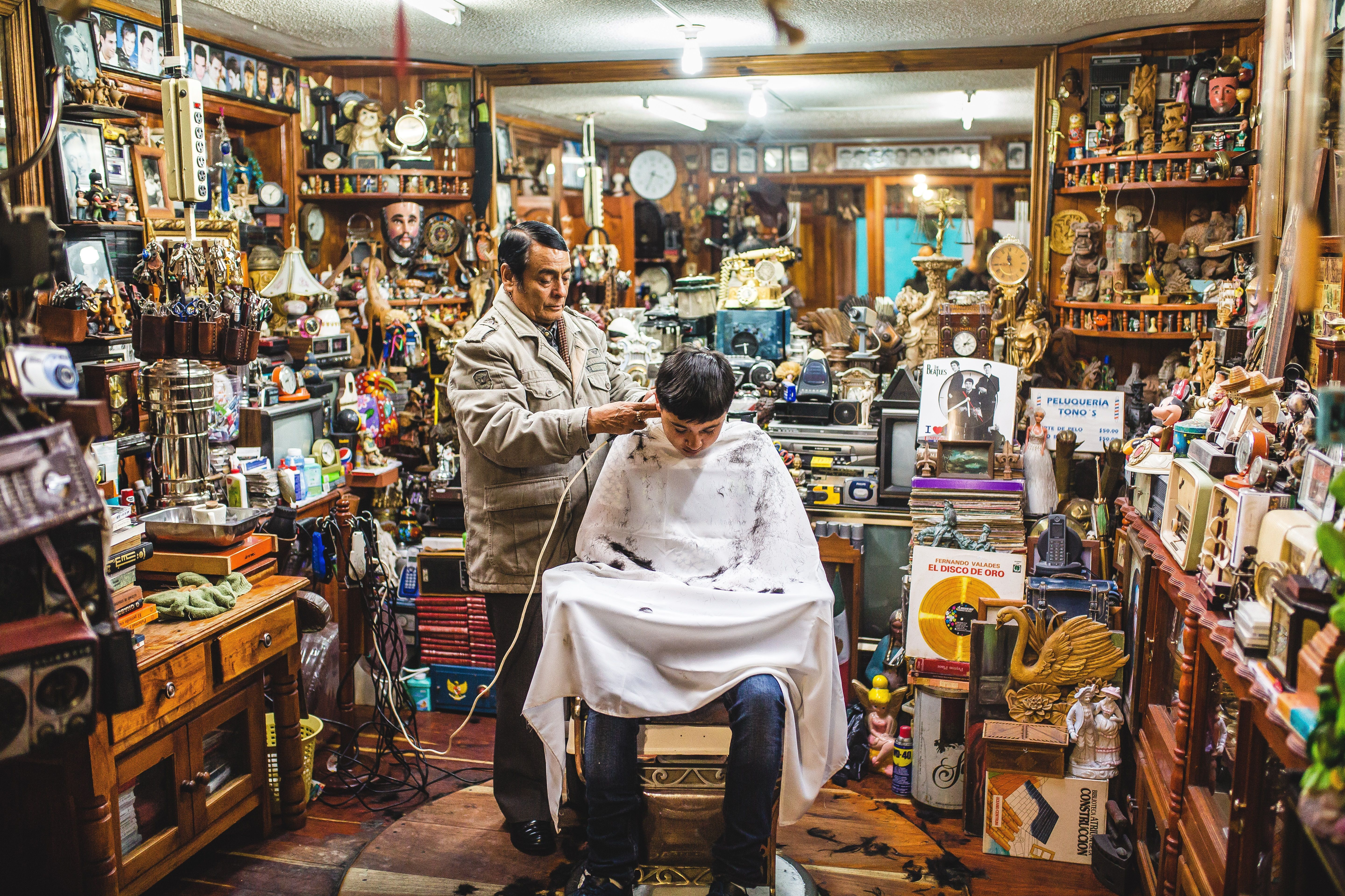 A barber cuts a young man's hair in his shop in Mexico. He has worked out of the same shop for more than 40 years, collecting interesting and unique items for his collection along the way.