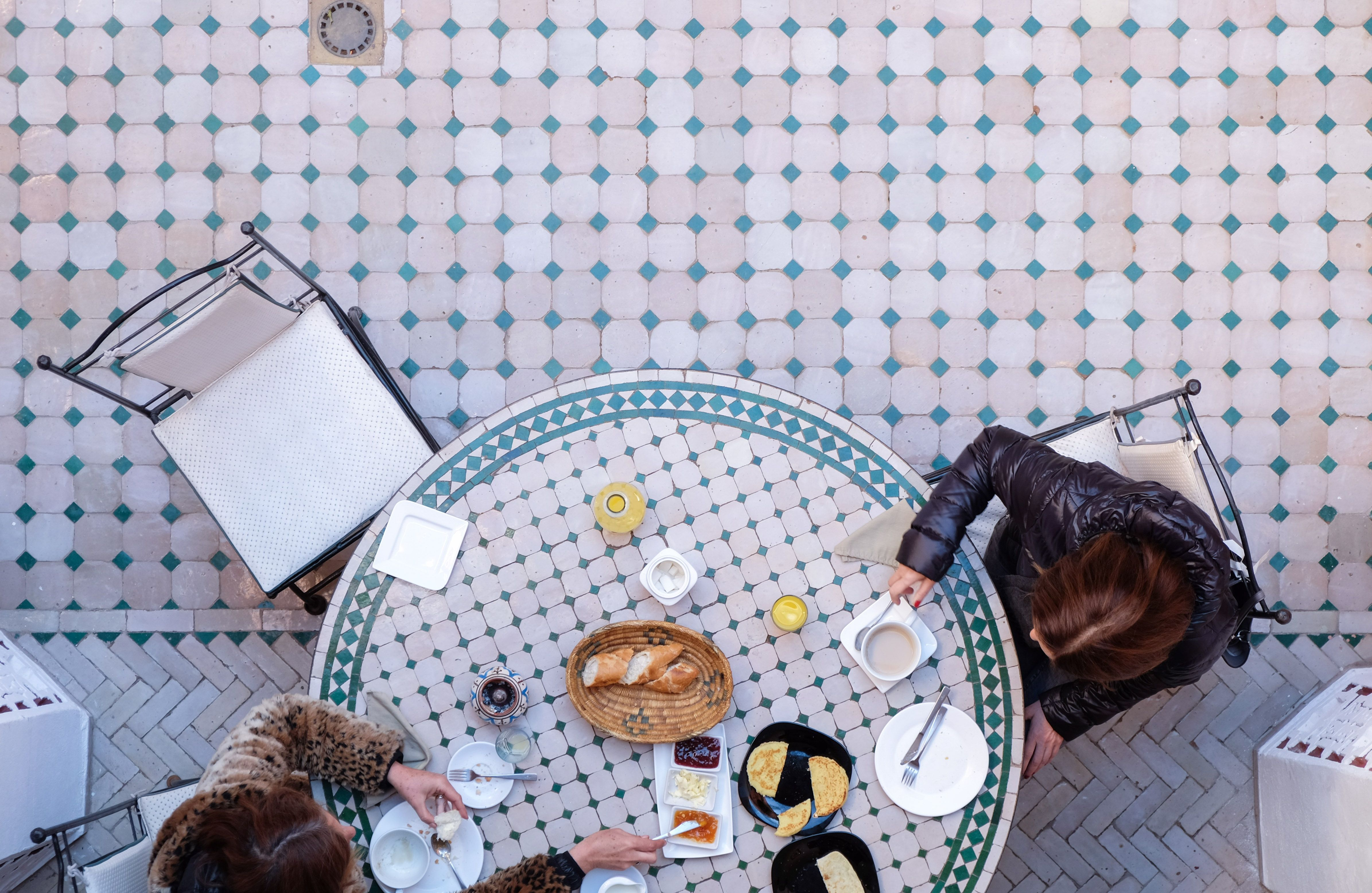 Morocco is known for its zellige, the handmade tiles that form interesting and colorful patterns. In this photo, taken in Marrakesh, women take a snack break on a floor and table featuring the art form.